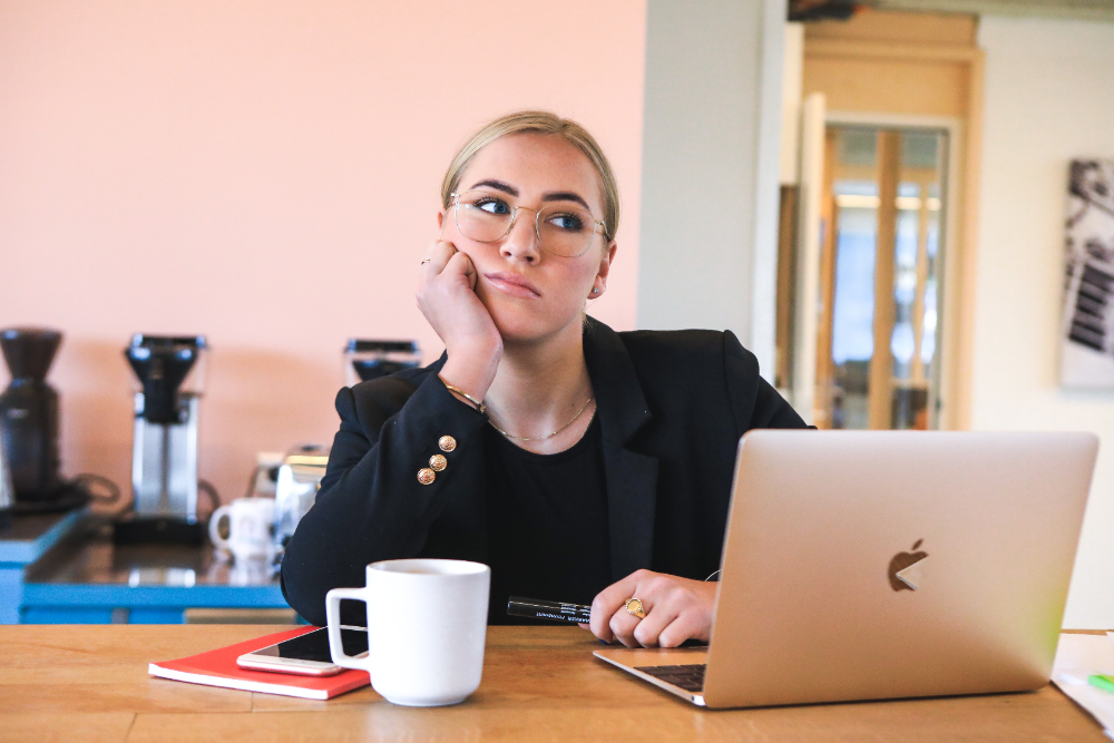 bored woman in black with mug and laptop