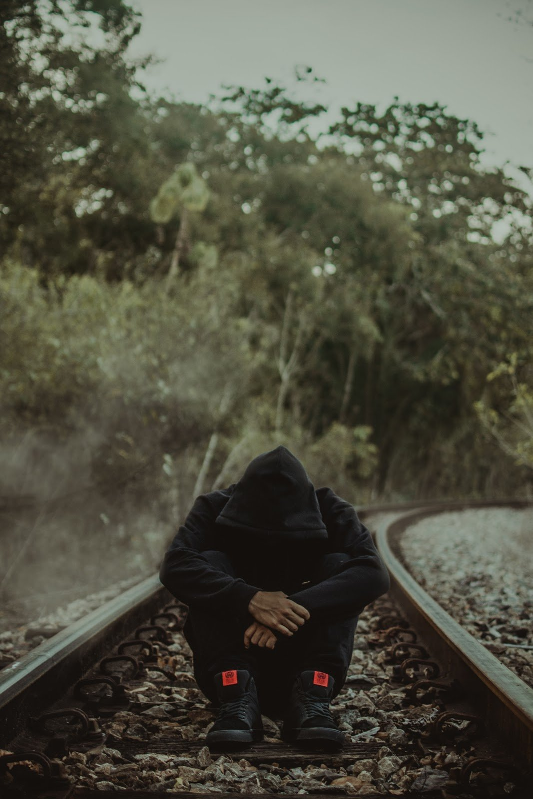 man sitting on rail tracks
