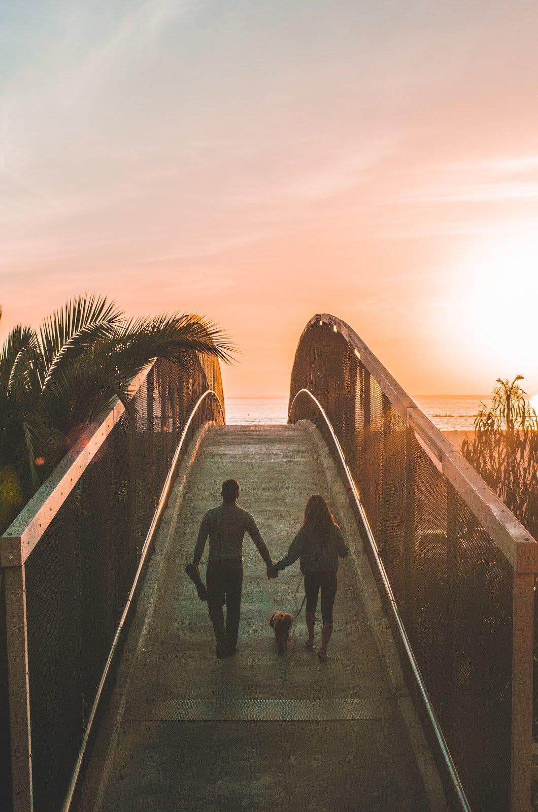 man woman walking dog on bridge