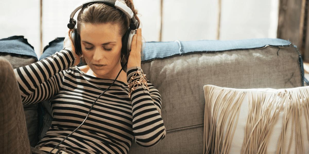 Music Reviewer seduto sul divano e ascoltando musica a pagamento