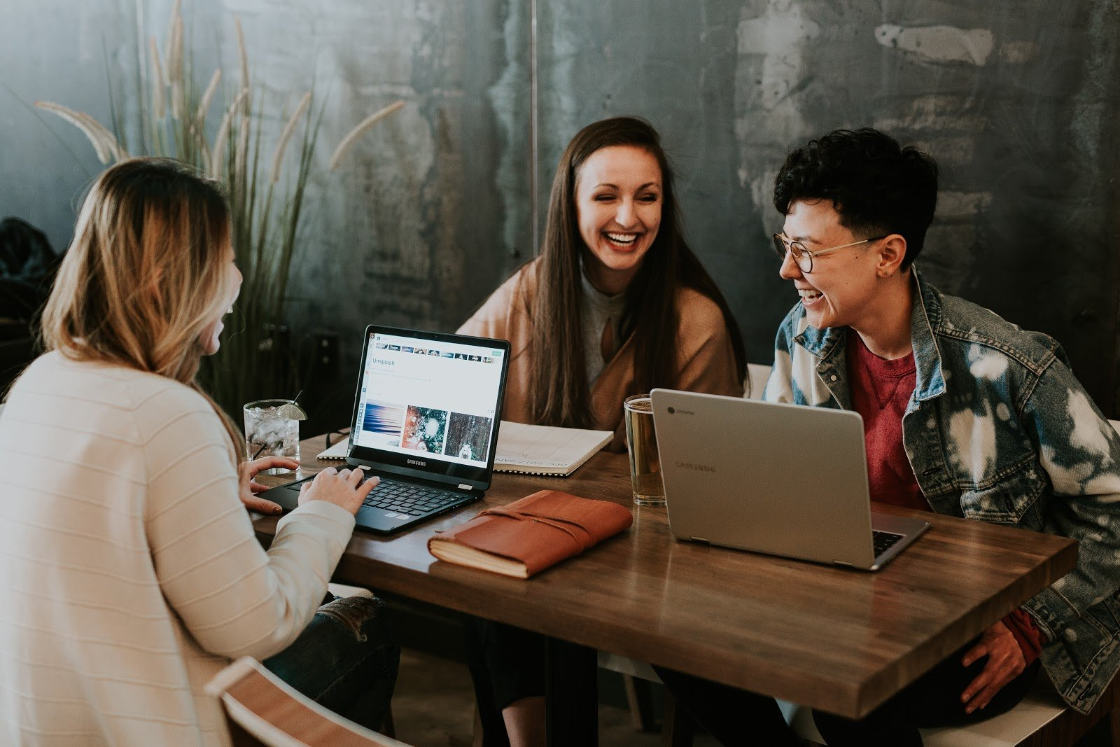 three women working on laptops laughing