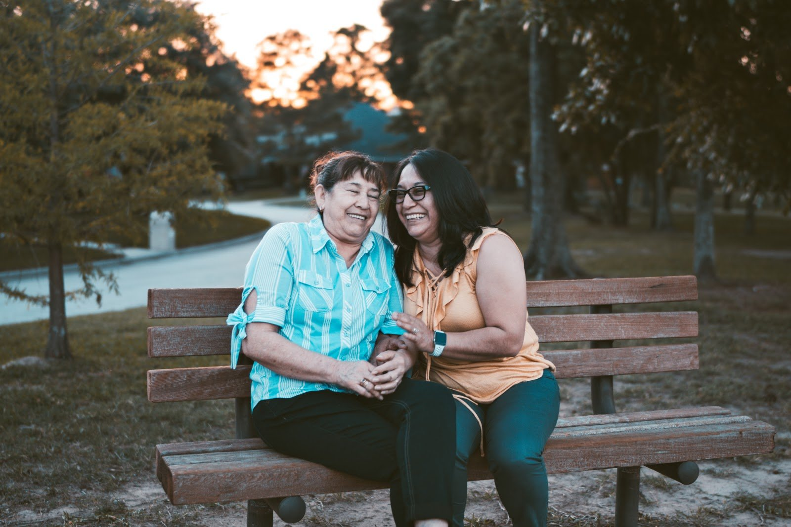 two women on park bench laughing