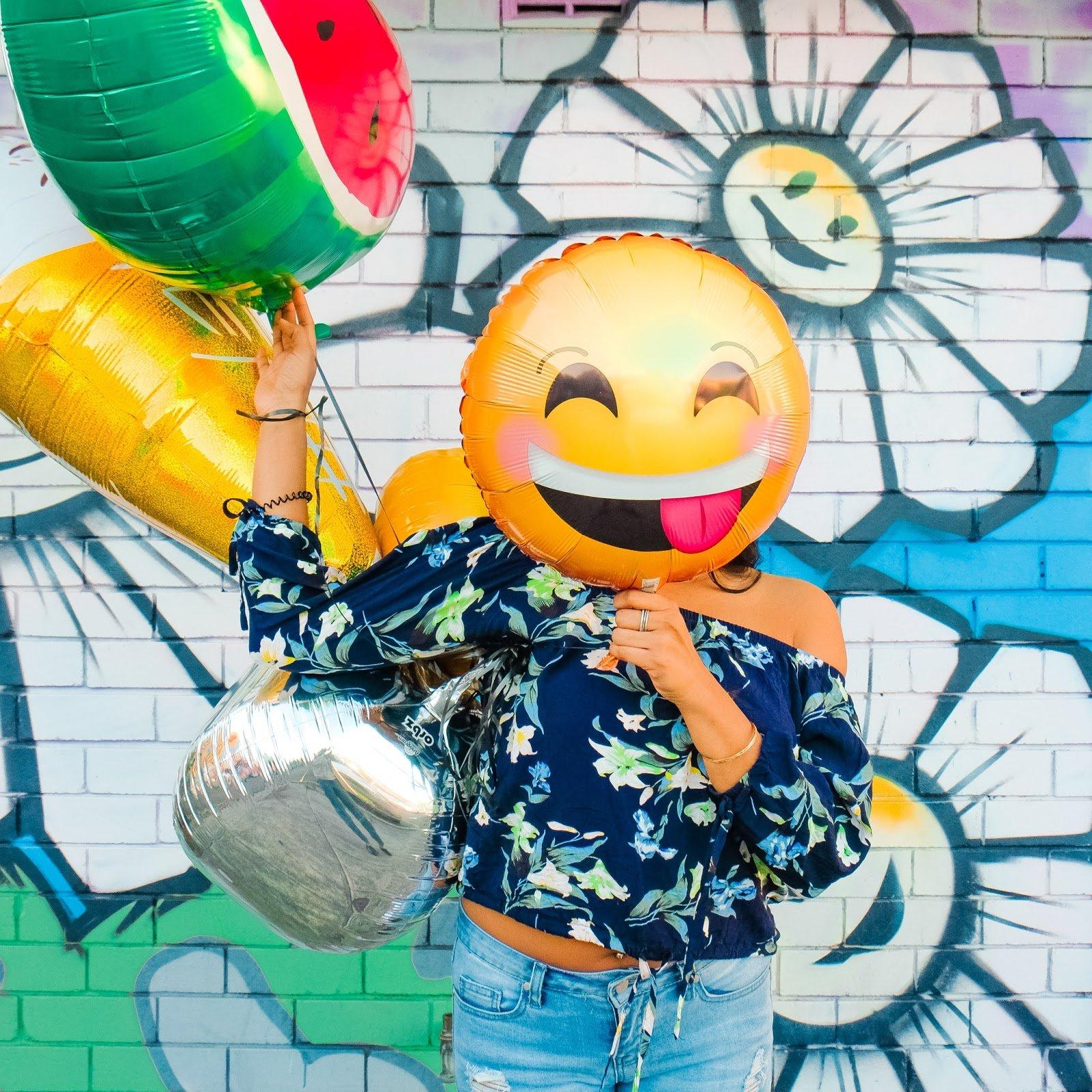 woman holding smiley face emoji baloon