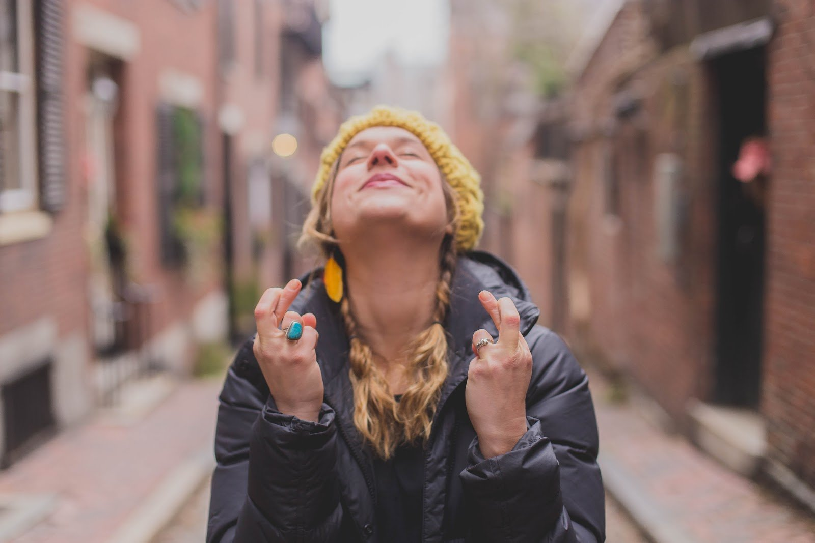 woman on street with fingers crossed